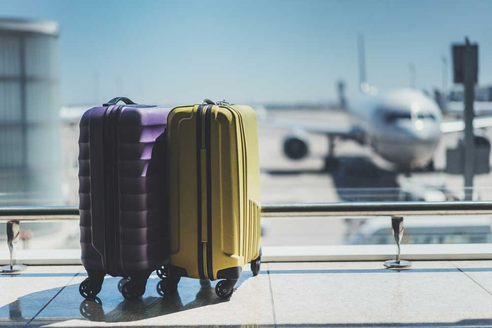 suitcases sit in front of departure gate.
