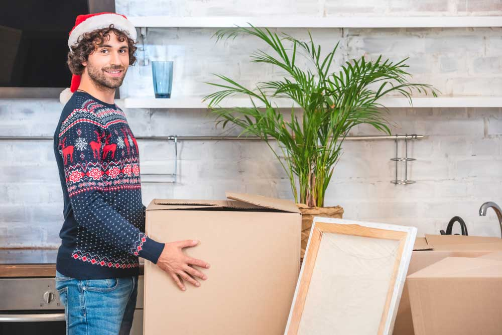 young man organizing moving boxes around home